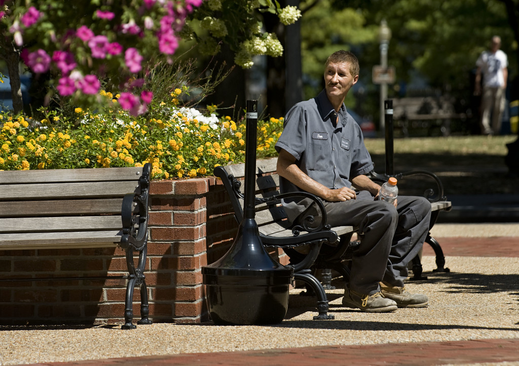 Don Grandstaff, of Front Royal, sits near some colorful flowers along Main and Chester streets in Front Royal recently while he waits for a ride.  Rich Cooley/Daily