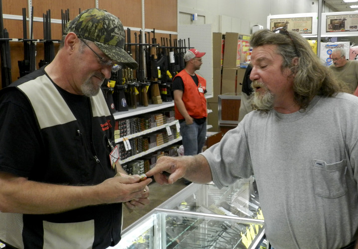 Mike Peters, left, gun barn manager at Rural King, tells Billy Lucas, of Front Royal, about a type of ammunition Monday during the store's soft opening. Nathan Budryk/Daily