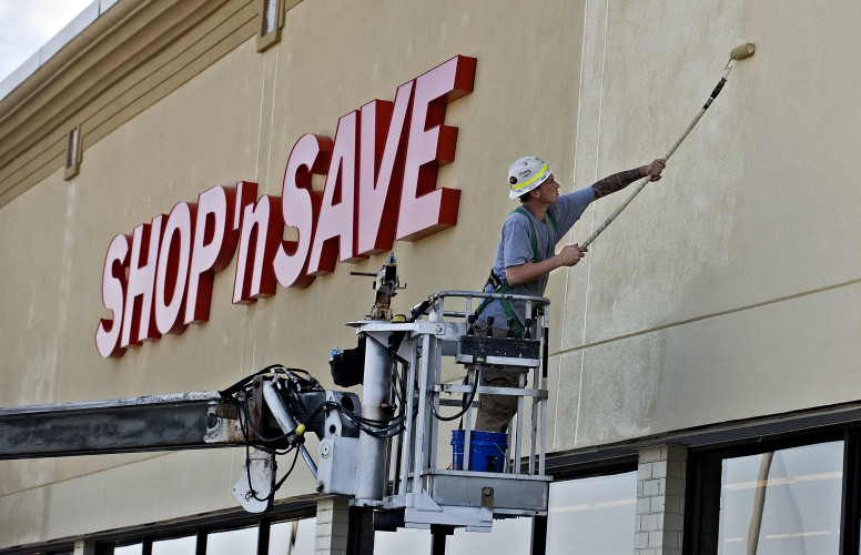 Anthony Allen, a sign installer for Talley Sign Company in Richmond, paints outside the new Front Royal Shop 'n Save store in September. Food Lion stores in Stephens City, Winchester and Berryville also reopened last fall as Shop 'n Save stores. Rich Cooley/Daily