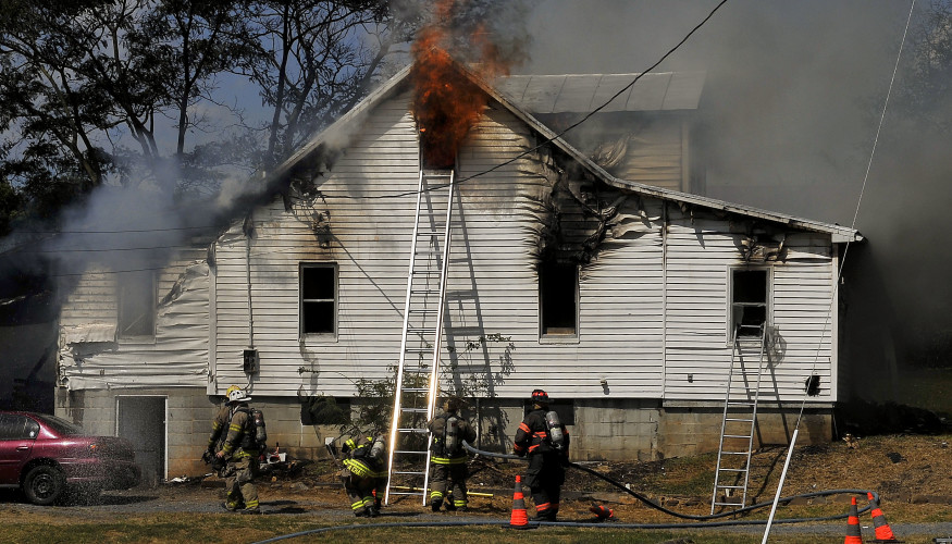 Flames pour out of the second floor window of a home on Stultz Gap Road west of Edinburg on Tuesday. Jake Zuckerman/Daily