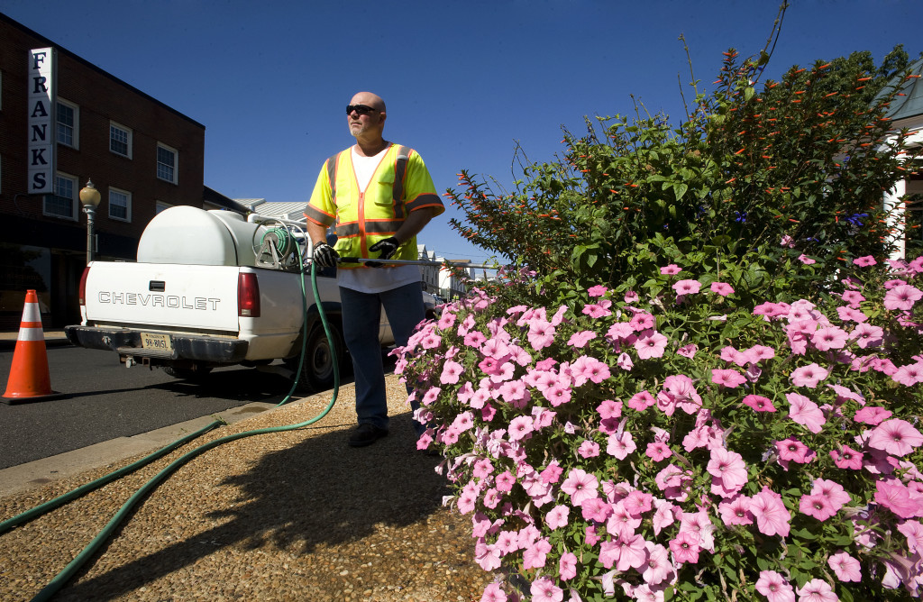 Paul Smith, an employee of the Town of Front Royal's horticulture department, waters planters along East Main and Chester streets on a recent sunny, hot day.  Summer's temperatures are starting to cool as fall draws near. Today's high will be near 80.  Rich Cooley/Daily