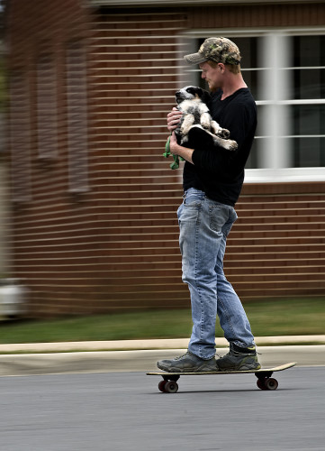 Sam Harper, 23, of Strasburg, takes his dog Sawyer for a skateboard ride along West Queen Street near his home in Strasburg on Friday.  Rich Cooley/Daily