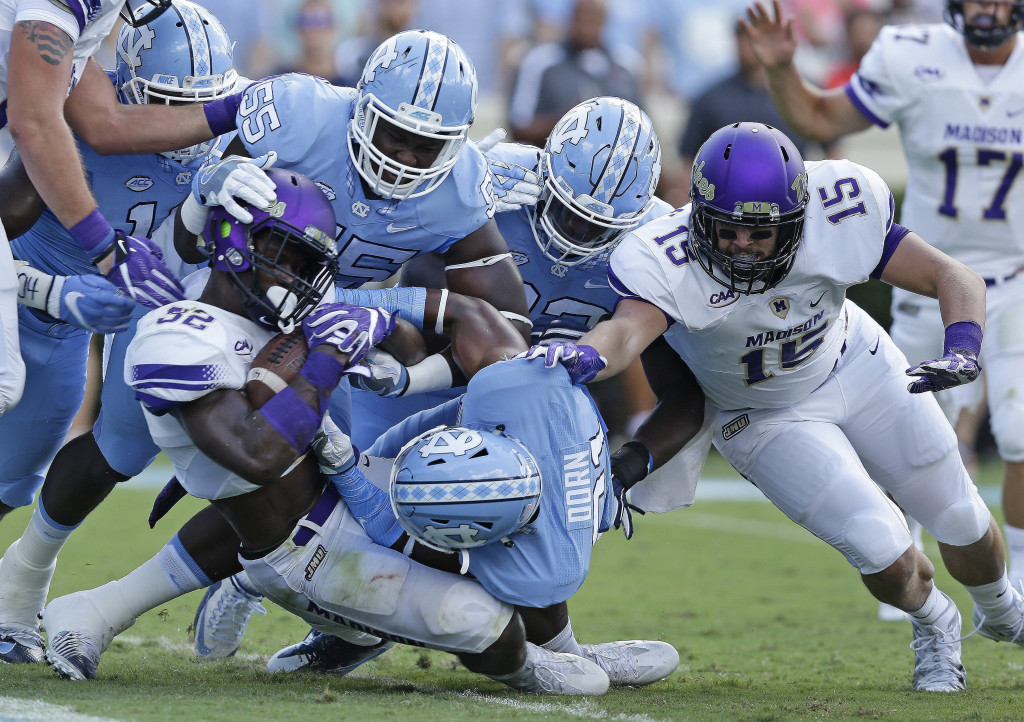 North Carolina's Jason Strowbridge (55), Cayson Collins and Myles Dorn try to stop James Madison's Khalid Abdullah (32) from scoring as James Madison's Daniel Schiele (15) blocks in the first half of their game Saturday in Chapel Hill, N.C.  Abdullah scored on the play. The Dukes had 495 yards of offense in the 56-28 loss. AP