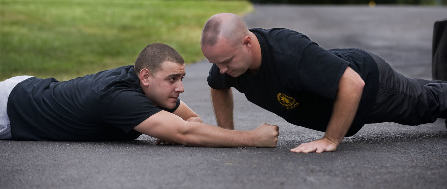 Woodstock Police Department patrolman D.J. Dunivan, left, monitors his coworker, patrolman Ben DeMay, as he executes pushups as part of their physical fitness regiment. The police department has implemented a physical fitness and wellness program that has made staff healthier and more fit.    Rich Cooley/Daily