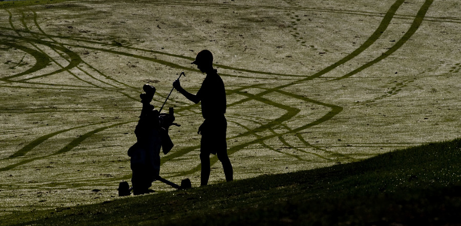Sherando's Brett Loy puts away a club in this early morning scene among golf cart shadows during the Conference 21 West tournament held at Blue Ridge Shadows golf course on Thursday.  Rich Cooley/Daily