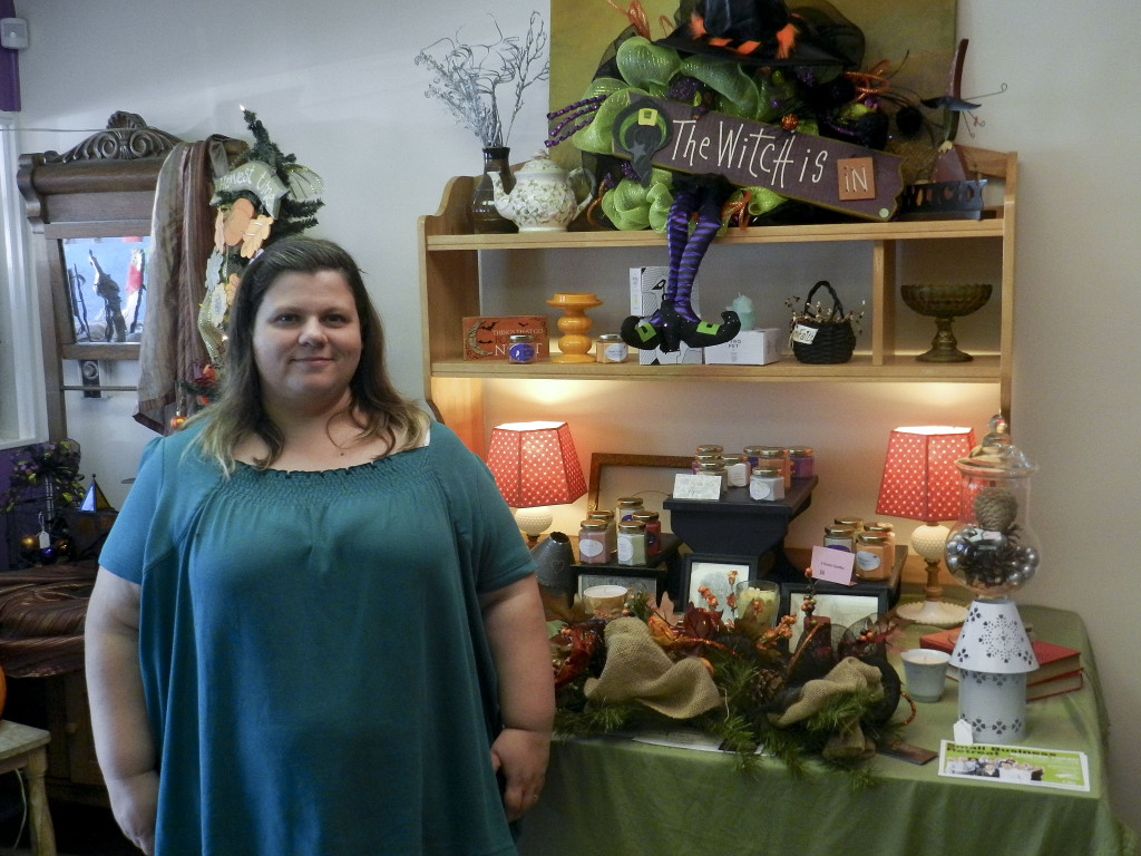 Debbie Ritenour, owner of Simply Divine Candles and Decor, stands in front of some handmade candles and a homemade wreath in her store. She is holding a  grand re-opening event Saturday at the store's new location at 150 E. King St., Strasburg. Nathan Budryk/Daily