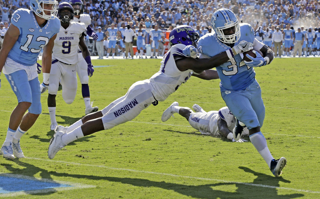 James Madison University's Jimmy Moreland tries to tackle North Carolina's Elijah Hood as he runs for a touchdown in the first half of their game in Chapel Hill, North Carolina, on Sept. 17. The Dukes play at Maine today. AP