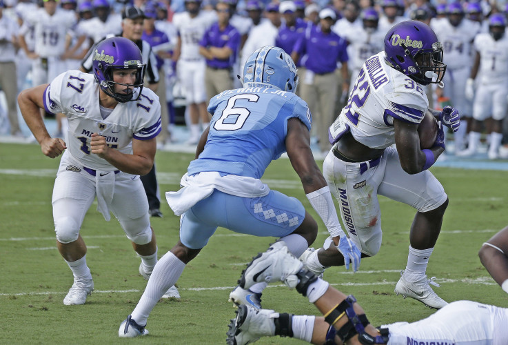 JMU's Khalid Abdullah (32) takes the handoff from quarterback Bryan Schor (17) in their game against North Carolina on Sept. 17 in Chapel Hill, North Carolina. Abdullah was named the CAA Offensive Player of the Week this week after his 172-yard performance against Maine on Saturday. AP