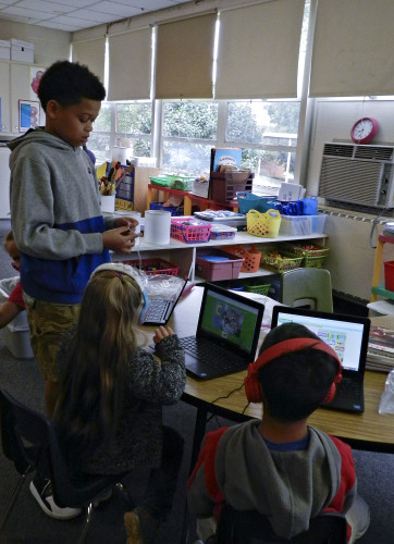 Kaleb Smith, left, a Ressie Jeffries Elementary School fifth grader and president of the school's chapter of the National Elementary Honor Society, helps kindergarten students with their morning work on computers before class started Wednesday morning. Rachel Mahoney/Daily