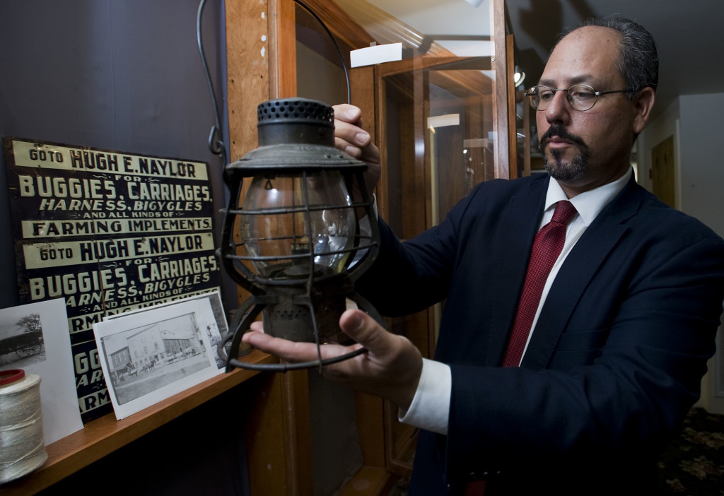 Patrick Farris, executive director of the Warren Heritage Society, holds an old railroad lantern dating to the early 1900s that is part of a new yearlong transportation display at the Warren Heritage Society in Front Royal. The lantern, on loan from Front Royal resident Ron Santmyers, was used by his late grandfather, who worked for Norfolk and Western Railroad.   Rich Cooley/Daily