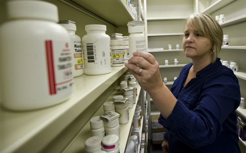 Michelle Rimel, owner of Peoples Drugstore in Strasburg, pulls a drug bottle off the shelf of her store Thursday. Rimel, the store's pharmacist, is selling the century old business to Rite-Aid, and the building's owner has put the King Street store up for sale.  Rich Cooley/Daily