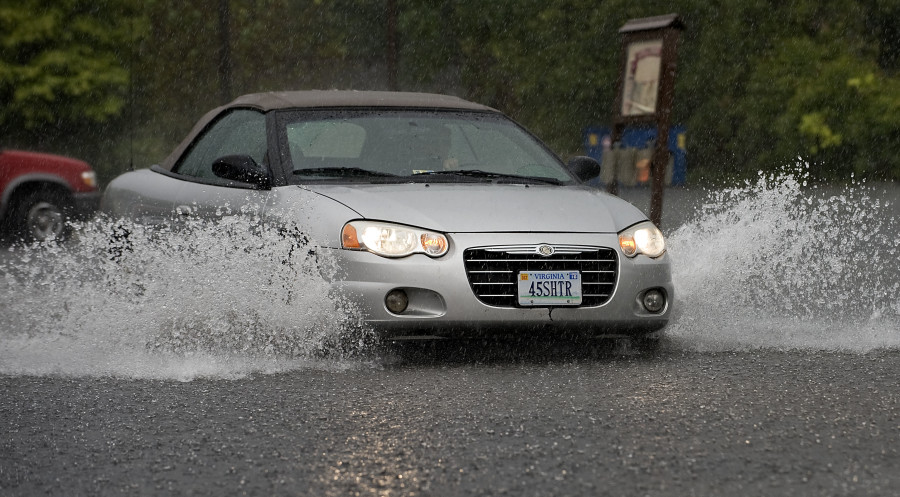 A car travels through the flooded parking lot behind the Strasburg Emporium on Thursday afternoon.  Rich Cooley/Daily