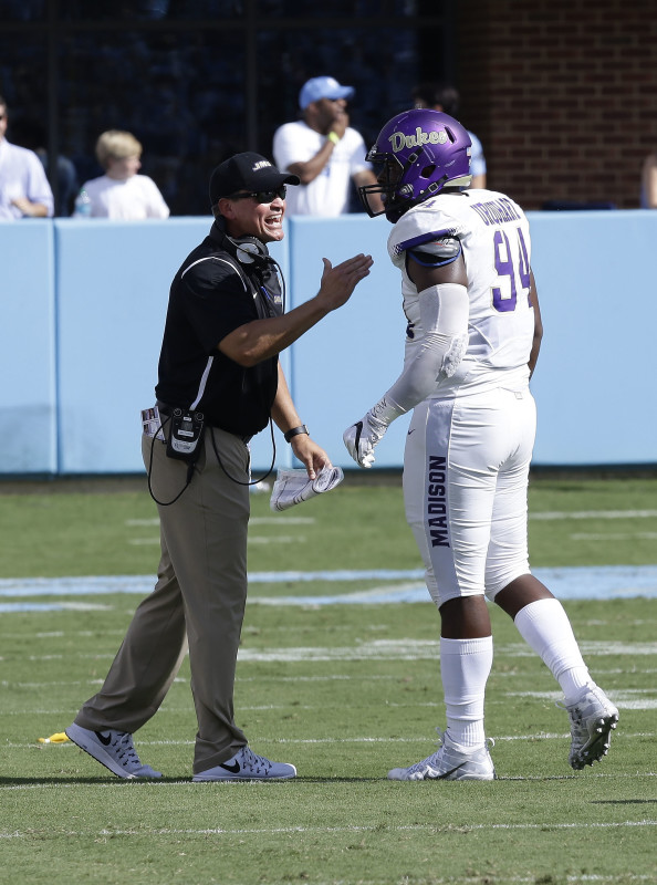 James Madison head coach Mike Houston speaks with Cornell Urquhart in the first half of their college football game against North Carolina on Sept. 17 in Chapel Hill, North Carolina. AP file