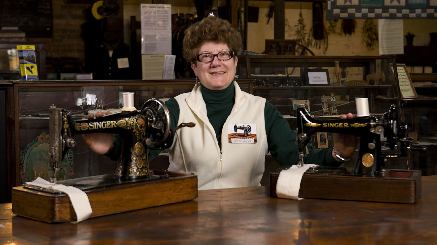 Joan Grewe, of Front Royal, sits beside her hand crank sewing machines on display at the Strasburg Museum through the end of October. At left is a Singer 1924 Red Eye Model 66, and at right is a 1930 Singer Model 128K.  Rich Cooley/Daily