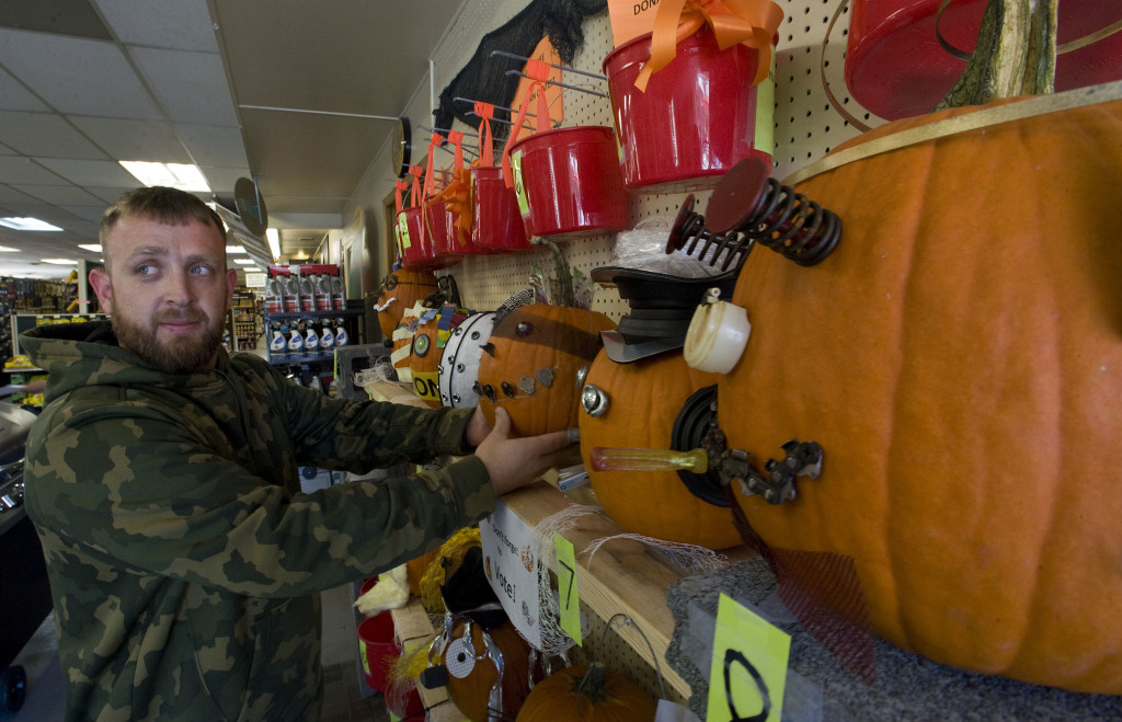 Aaron Barnes, a sales associate at Borden Lumber Company in Strasburg, places one of the store's 15 decorated pumpkins on a shelf on Monday. The pumpkins were designed by employees using available hardware around the store. Customers are encouraged to vote for their favorite pumpkin by dropping change into a bucket, and bid to buy their favorite pumpkin. Proceeds from the fundraiser will go to the Strasburg Local Relief Fund – a joint effort by Strasburg Presbyterian Church, Strasburg Christian Church, Strasburg United Methodist and St. Paul Lutheran Church. The voting and bidding ends Oct. 28.  Rich Cooley/Daily