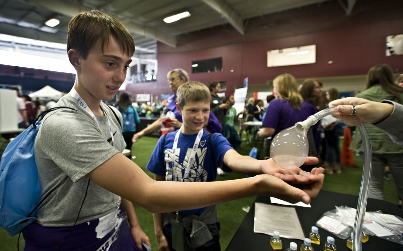 Signal Knob Middle School students Hayden Fravel, left, and Griffin Curcen, both 12, stretch out their hands to catch a bubble from Thermo Fisher Scientific's booth at the Worlds of Work Expo held Wednesday at the Body Renew Fitness Sports Center in Winchester. Thermo Fisher, of Middletown, used dry ice, warm water and soap to create the gas bubble.  Rich Cooley/Daily