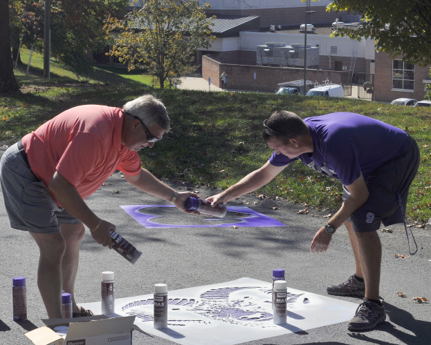 "Strasburg Mayor Rich Orndorff Jr., left, hands a can of spray paint to Strasburg High School Athletic Director Matt Hiserman to finish up stenciling a ram's head for the school's new ""Ram Trail"" on Tuesday. The trail of painted ram's heads will extend to the intersection of the town's King and Holiday streets. Jake Zuckerman/Daily"