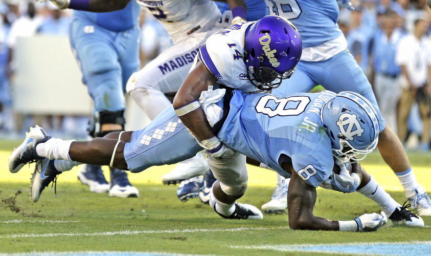 James Madison's Taylor Reynolds (14) tackles North Carolina's T.J. Logan (8) during their game on Sept. 17 in Chapel Hill, North Carolina. Reynolds has played a key role in JMU's success this season. AP file