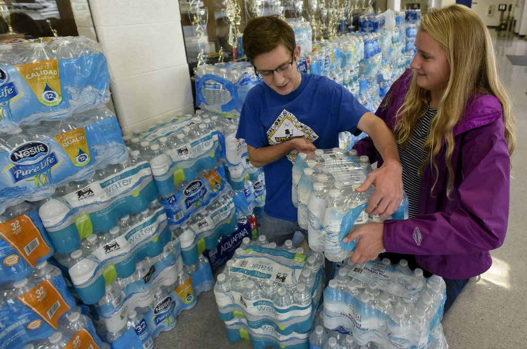 Robby Phillips, 17, left, of Woodstock, and Ashley Funkhouser, 16, of Edinburg, stack cases of water outside the gymnasium area at Central High School on Friday. The pair are members of the Shenandoah County Biomedical Science Academy, which collected 200 cases of water for the town of Luckworth, North Carolina.  Rich Cooley/Daily
