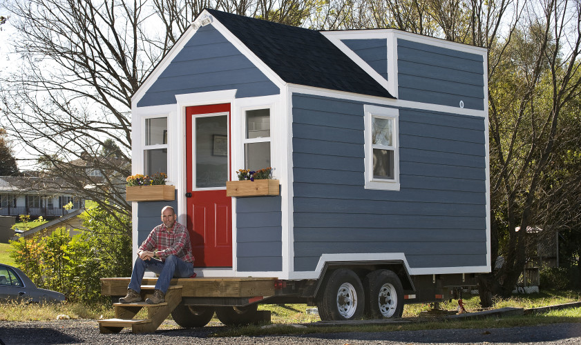 Custom home contractor H.B. Sager sits on the steps outside a tiny home he constructed. It's parked outside Shenandoah Woodworks in Maurertown. The home, which is mounted on a trailer, can be easily transported as an RV. Rich Cooley/Daily