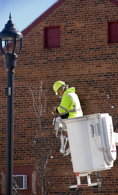 Ricky Crawford, a town of Strasburg town maintenance worker, winds Christmas lights around the trees on West King Street on Tuesday. Crawford and his coworkers were getting a jump on the annual project while the weather was warm.  Rich Cooley/Daily