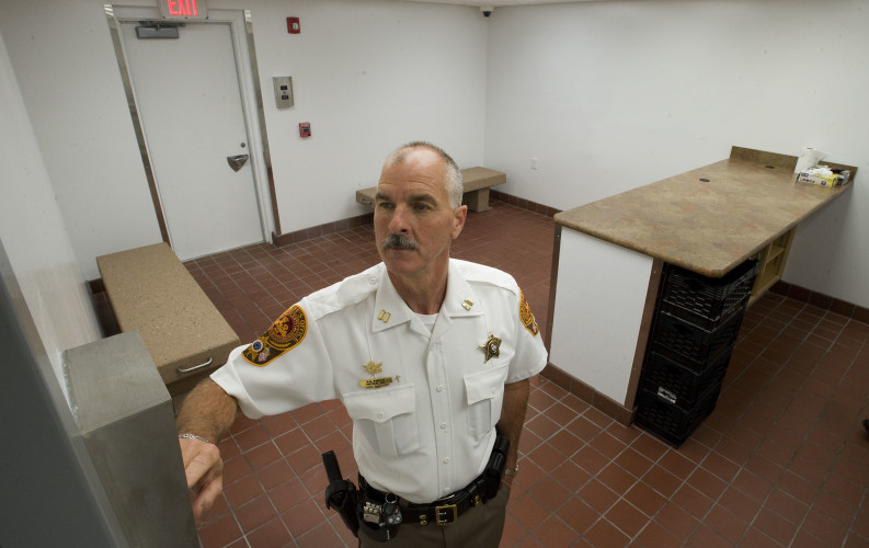 Warren County Sheriff's Office Capt. Roger Vorous uses the call box to open a secured door in the new prisoner processing area. The call box relays voice and video coverage at doors inside the facility. Personnel in the  processing control center control door locks, adding extra security.  Rich Cooley/Daily