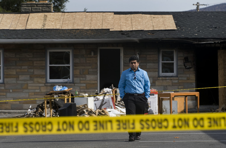 Shiv Patel, manager of the Sunshine Inn in Front Royal, walks past debris in the parking lot of the South Royal Avenue business Monday afternoon following a fire on Saturday.  Rich Cooley/Daily