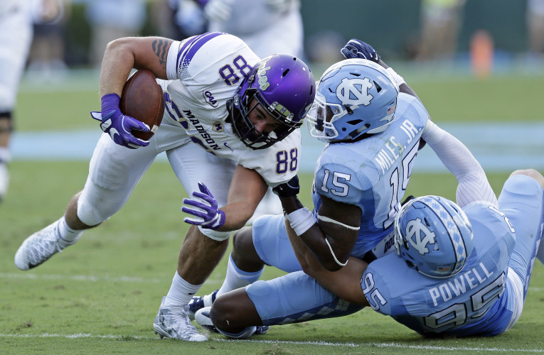 North Carolina's Donnie Miles (15) and Tyler Powell (95) tackle James Madison's Jonathan Kloosterman (88) in the first half of their game in Chapel Hill, N.C., on Sept. 17. AP file.