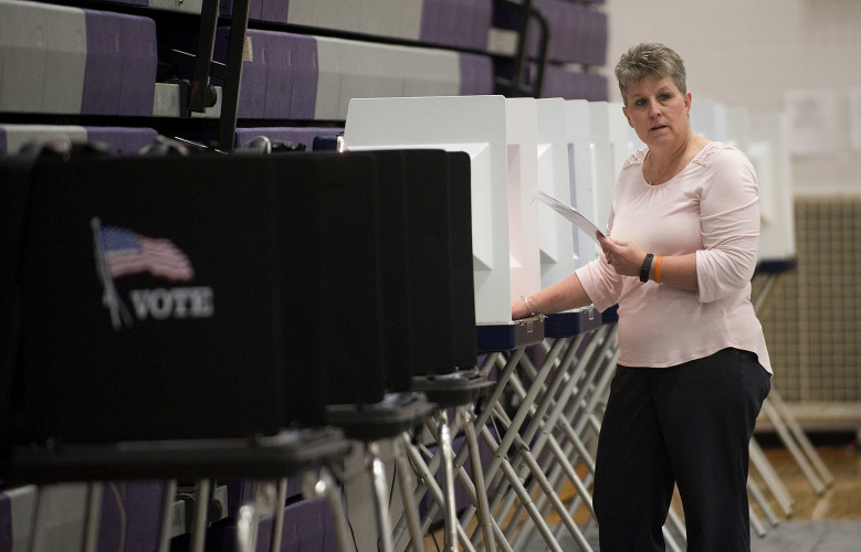Election official Teresa Orndorff works on lining up polling booths inside Strasburg High School on Monday as officials prepare for today's elections.   Rich Cooley/Daily
