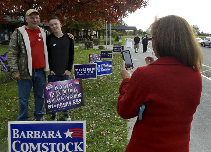 Kelly Thatcher, who won a seat on the Stephens City Town Council on Tuesday, takes a photo of Chris and Cole Fletcher outside of the Robert E. Aylor Middle School polling place. Rachel Mahoney/Daily