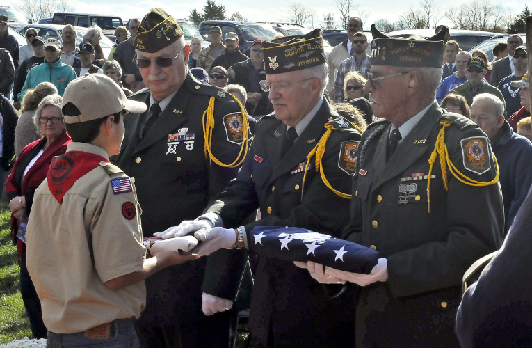 A member of the Virginia Honor Guard hands the Virginia flag to Jimmy Haskins, left, to raise at Middletown's new Veterans' Memorial Wall on Friday.  Jake Zuckerman/Daily
