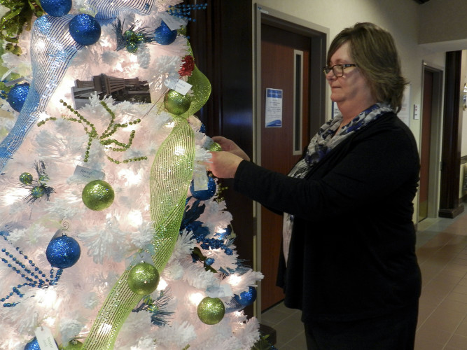 Judy Gribble, LifeNet Health ambassador and liver transplant recipient, hangs an ornament on the Tree of Remembrance at Winchester Medical Center in honor of those who have donated an organ. Kaley Toy/Daily
