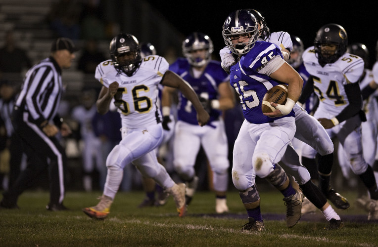 Strasburg's Josh Pritchett looks for running room as King William's Jerean Rogers pursues him during the first quarter of Friday night's game in Strasburg.  Rich Cooley/Daily
