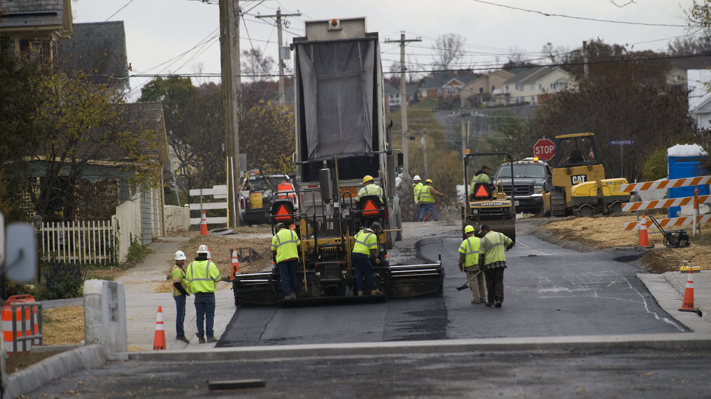Construction crews pave a section of Queen Street in Strasburg last month.  Fielder's Choice Enterprises Inc., of Charlottesville, replaced the bridge with a wider crossing and approaches and install sidewalks and drainage improvements. The project, which started last April, cost $2.2 million and was funded through state and federal funds.  Rich Cooley/Daily