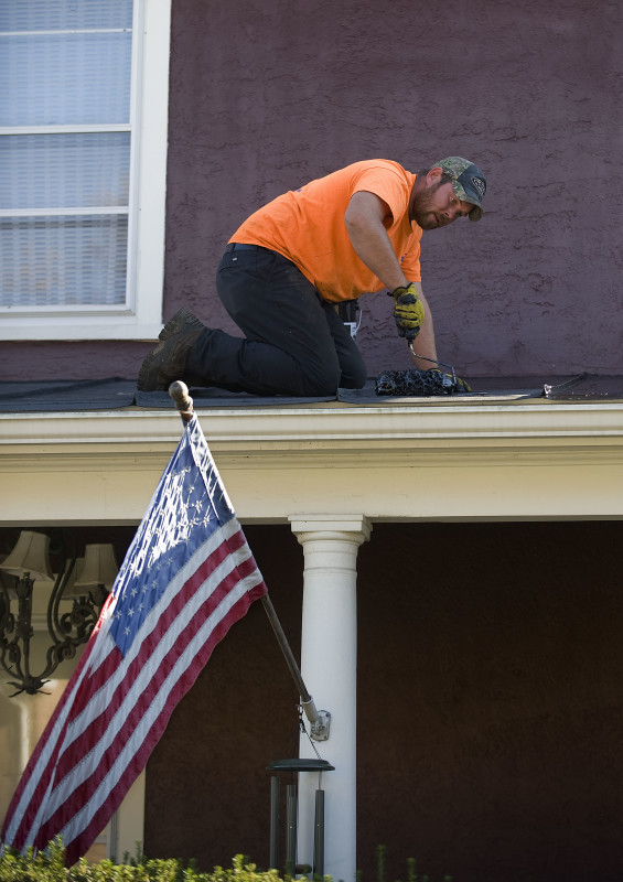 Contractor Charles Seaford of Linden rolls tar on this metal roof along Luray Avenue in Front Royal. The roof received its winter coat as warm weather is expected to come to a close this weekend and temperatures are forecasted to plummet Saturday evening. Rich Cooley/Daily