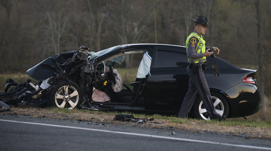 State trooper K.J. Orr walks past a car that collided with a tractor-trailer Thursday evening on Remount Road in Warren County near the intersection with Summit Point Drive.  Rich Cooley/Daily
