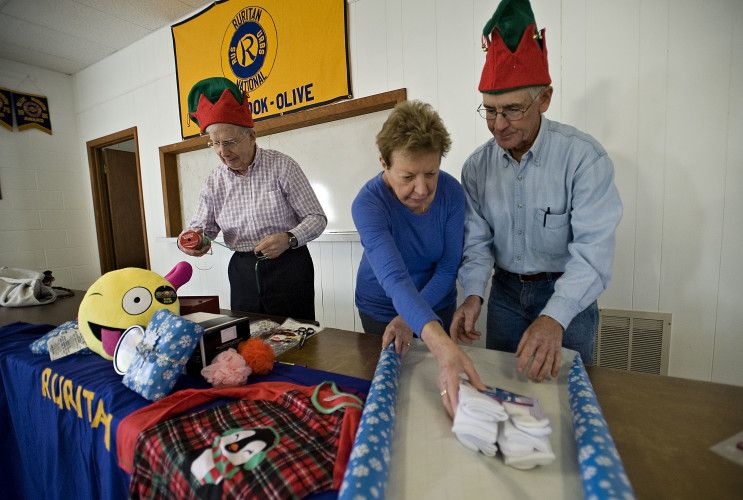 John Gaunt, left, treasurer of the Empty Stocking Fund, pulls out some ribbon while Barbara Orlando, center, member of the Maur-Brook Olive Ruritan Club, and Dennis Morris, right, Zone Four governor of area Ruritan clubs and coordinator of the Empty Stocking Fund,  wrap a bundle of socks inside the Maur-Brook Olive Ruritan Club headquarters in Mount Olive recently. Rich Cooley/Daily