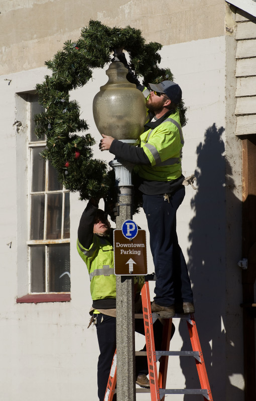 Preston Toms, left, and Chris Rowland, both linemen with the Town of Front Royal's Electric Department, install Christmas wreaths on street lights along Main Street on Monday morning. Rich Cooley/Daily