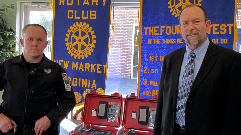 New Market Police Officer Greg Foss, at left, is presented two automated external defibrillators by New Market Rotary Club President Patrick Dauer.  Courtesy photo