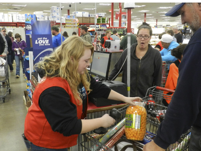 Mary Helen Ritchie, who usually works in the Rural King's agriculture department, filled in as an emergency cashier Friday to help the store try to keep up with the flood of customers as she checks out Michelle Dugan and Thomas Polk of Winchester.  Nathan Budryk/Daily