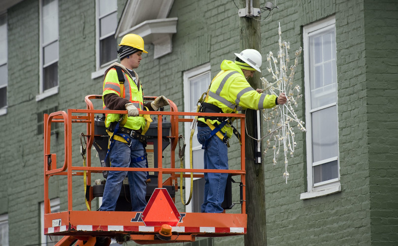 Adam Palm, left, and Wally Cross, both Strasburg town maintenance employees, hang a snowflake along a pole at the corner of King and Massanutten streets. The crew has been busy decorating the town's utility poles along King Street this week. Rich Cooley/Daily