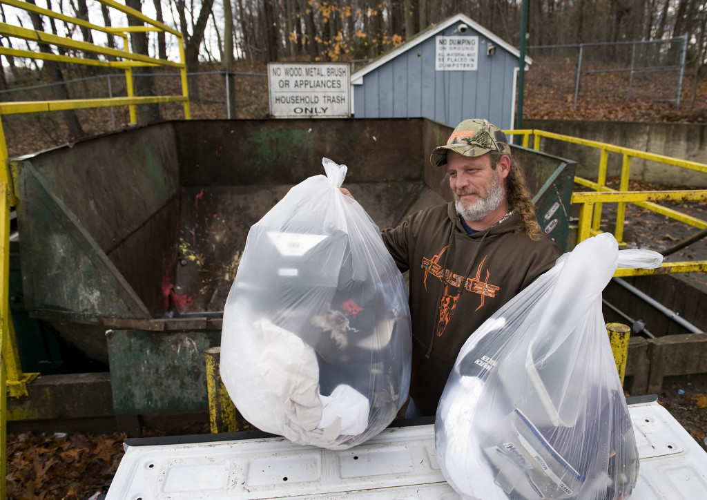 Scott Sager, of Strasburg, unloads his household trash off the back of his pickup truck at Shenandoah County's compactor and recycle center site on U.S. Route 55 in Strasburg on Tuesday. The county has been enforcing illegal dumping at its 15 public convenience sites for refuse and recycling. Rich Cooley/Daily