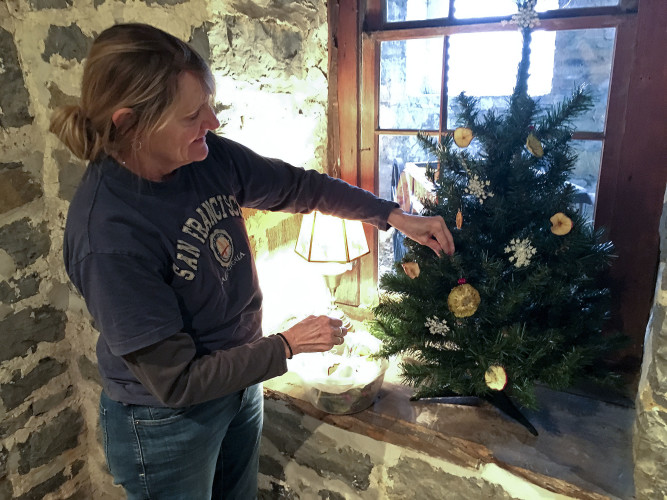 "Master gardener Rose Fairman decorates a tree inside the Belle Grove Plantation mansion. This year's house tours theme is ""O Tannenbaum – A Festival of Trees.""  Guided tours are offered from 10 a.m. to 4 p.m. Monday through Saturday.   Photo courtesy Belle Grove"