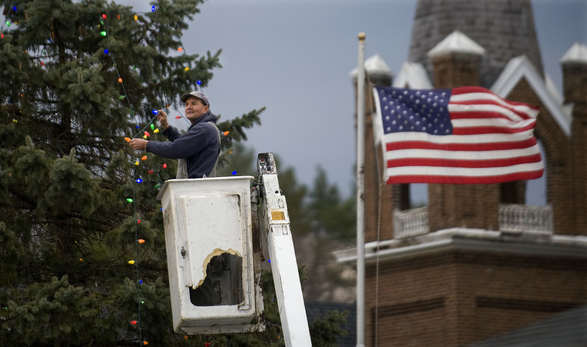 Kelly Keller, of Edinburg, fights a brisk wind as he strings a line of lights on this 28- foot blue spruce tree outside Toms Brook Fire Department on Friday. The town will hold a parade at 5 p.m. Sunday along with an auction and sale for a limited edition Christmas ornament created by artist Susie Wilburn.  Proceeds will benefit  the Alliance for Shelter.   Rich Cooley/Daily