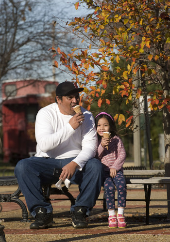 Mike Nagel and his daughter Kaila, 4, of Front Royal enjoy a sunny day and ice cream at the Front Royal Visitor's Center on East Main Street on Monday. Rich Cooley/Daily