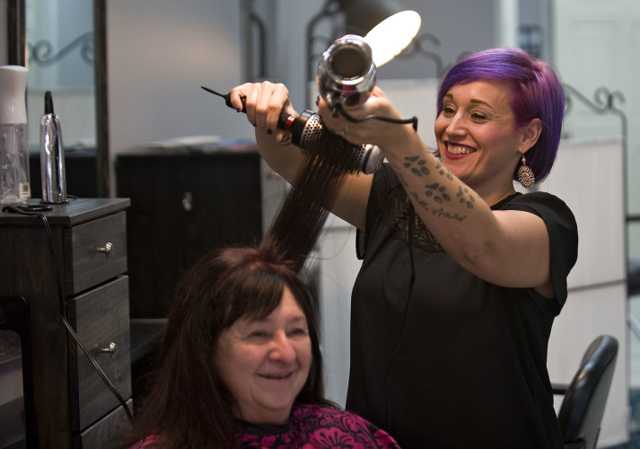 Tara Smith, owner and stylist at Hairspray Salon in Woodstock, styles her mother Brenda Pedersen's hair. Hairspray is celebrating its 10th anniversary on Saturday.  Rich Cooley/Daily