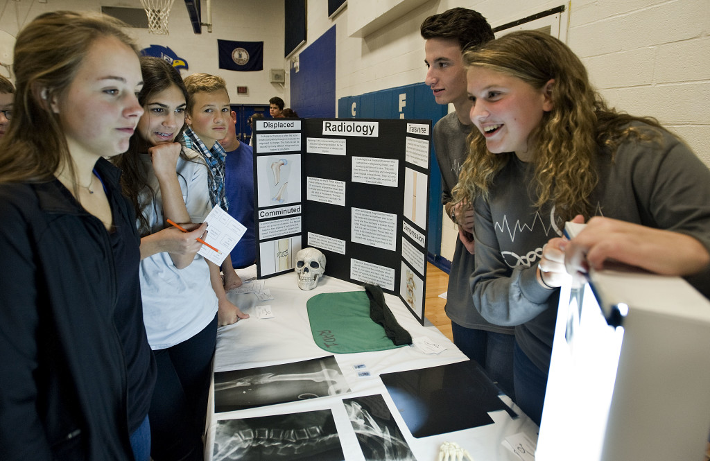 Alyssa Thorpe, 13, left, and Kristianna Rodriguez, 13, center, look at a radiology display hosted by Biomedical Science Academy students Garrett Estep, 15, a Stonewall Jackson High School student, and Mayia Rodriguez, 16, right, a Central High School student. Central HIgh School hosted the first of three biomedical expos to be held in Shenandoah County schools this week.  Rich Cooley/Daily