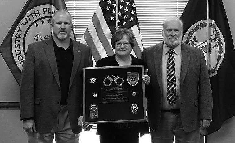 Rappahannock-Shenandoah-Warren Regional Jail Board Chairman Doug Stanley, left and jail Superintendent Bill Wilson, right, present Barbara C. Stickley with a display case that includes her badge from the Shenandoah County Sheriff's Office along with her badge from the jail.  Stickley, a correctional officer, is the first staff member to retire from the jail since it opened in 2014. Courtesy photo