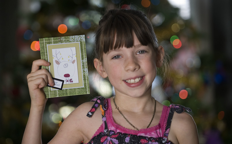 Madison Lowder, 8, of Strasburg, holds one of her reindeer Christmas cards. The young artist had a series of her cards professionally printed and has sold 100 packs of them in Strasburg. Rich Cooley/Daily
