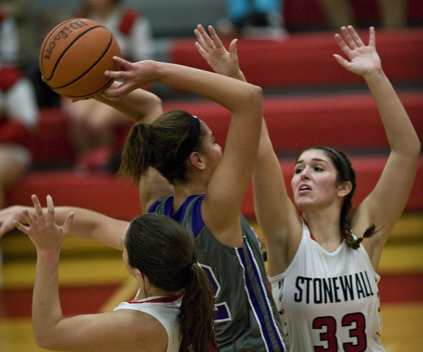 Stonewall's Sara Streett, left, and Madison Long put pressure on Strasburg's Christyan Reid during second quarter action Thursday night in Quicksburg. Rich Cooley/Daily